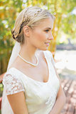 Pretty smiling blonde bride standing on a bridge