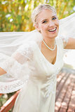 Pretty happy blonde bride holding her veil out smiling at camera