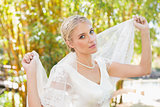 Pretty content blonde bride holding her veil out smiling at camera