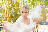 Calm blonde bride holding her veil out