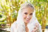 Beautiful blonde bride holding her veil smiling at camera