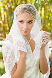 Beautiful blonde bride holding her veil