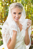 Beautiful blonde bride holding her veil looking at camera happily