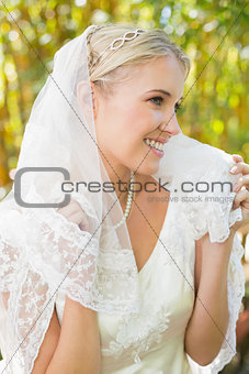 Beautiful blonde bride holding her veil and smiling