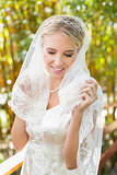 Beautiful blonde bride touching her veil and smiling