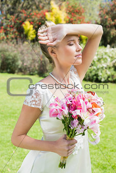 Beautiful blonde bride holding arm to forehead