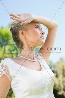 Pretty blonde bride holding arm to forehead on sunny day