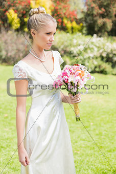 Pretty blonde bride holding lily bouquet