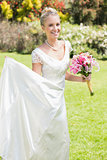 Pretty blonde bride holding lily bouquet and her dress
