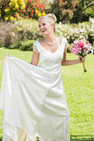 Pretty blonde bride holding bouquet and her dress