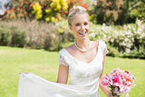 Beautiful blonde bride holding bouquet and her dress smiling at camera