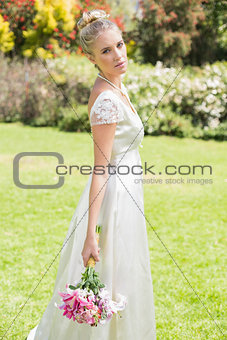 Beautiful blonde bride holding bouquet looking at camera