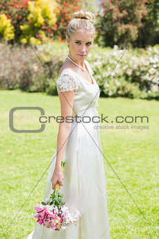 Beautiful blonde bride holding bouquet looking away
