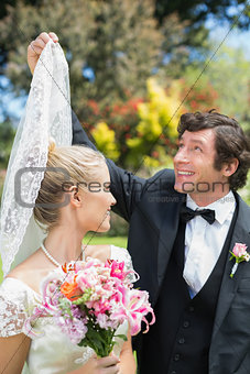 Groom holding his wifes veil smiling at each other