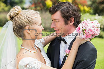 Attractive bride and groom hugging and smiling at each other
