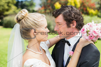 Attractive bride and groom embracing and looking at each other