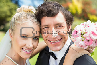 Attractive bride and groom smiling at camera