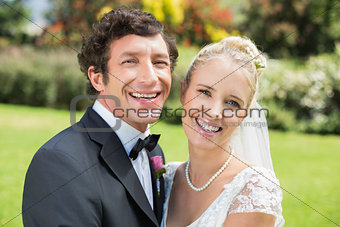Attractive bride and groom smiling at camera together