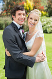 Attractive bride and groom smiling at camera and hugging