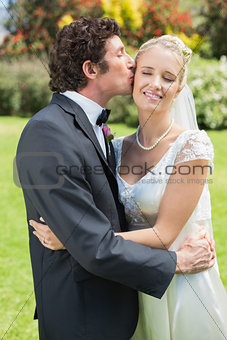 Groom kissing his pretty new wife on the cheek