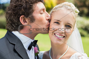 Groom kissing his pretty blonde wife on the cheek