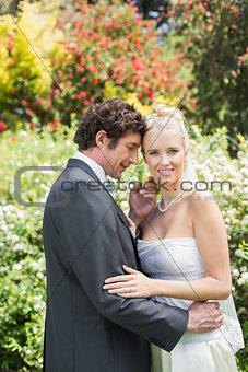 Romantic smiling newlyweds embracing looking at camera