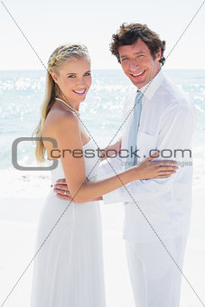 Romantic happy couple on their wedding day smiling at camera