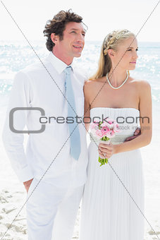 Couple standing together on their wedding day looking away