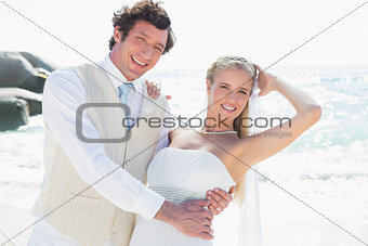 Groom holding his smiling new wife while dancing looking at camera