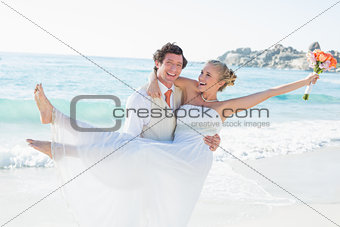 Laughing groom carrying his pretty blonde wife