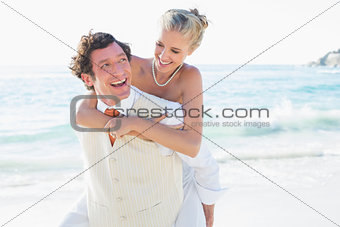 Smiling bride getting a piggy back from new husband