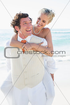 Smiling bride getting a piggy back from husband