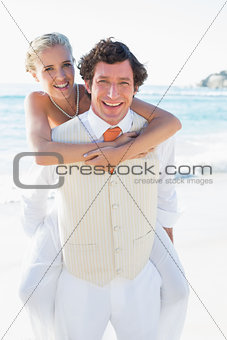 Happy bride getting a piggy back from husband
