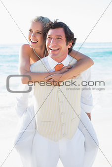 Happy bride getting a piggy back from handsome husband
