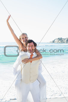 Waving bride getting a piggy back from husband smiling at camera