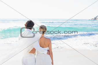 Newlyweds looking out to sea together
