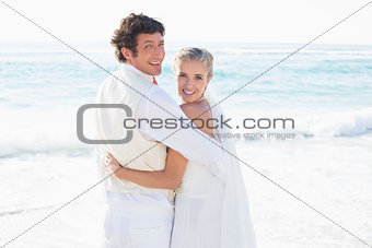 Newlyweds standing by the sea smiling at camera