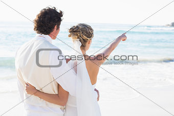 Newlyweds standing by the sea with wife pointing