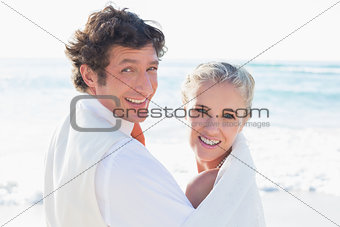 Newlyweds standing by the sea looking at the camera
