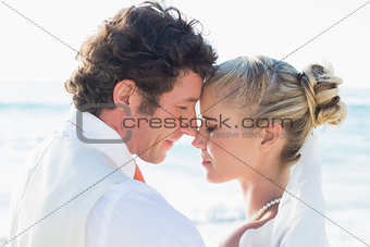 Newlyweds standing by the sea face to face