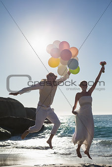 Groom holding balloons and bride holding bouquet jumping