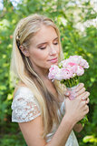 Blonde bride smelling her bouquet