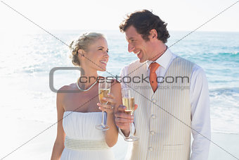 Young newlyweds toasting with champagne smiling at each other