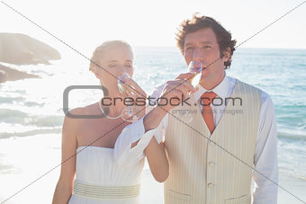 Young newlyweds drinking champagne linking arms