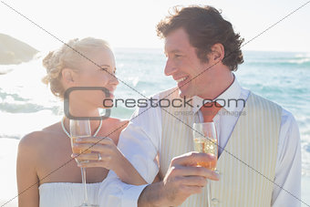 Young newlyweds having champagne linking arms
