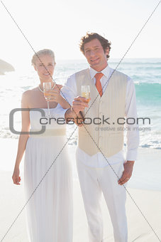 Happy newlyweds having champagne linking arms
