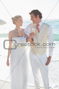 Smiling newlyweds having champagne linking arms