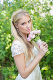 Blonde bride looking at camera holding pink bouquet