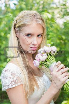 Blonde bride holding pink bouquet