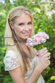 Blonde bride holding pink bouquet smiling at camera